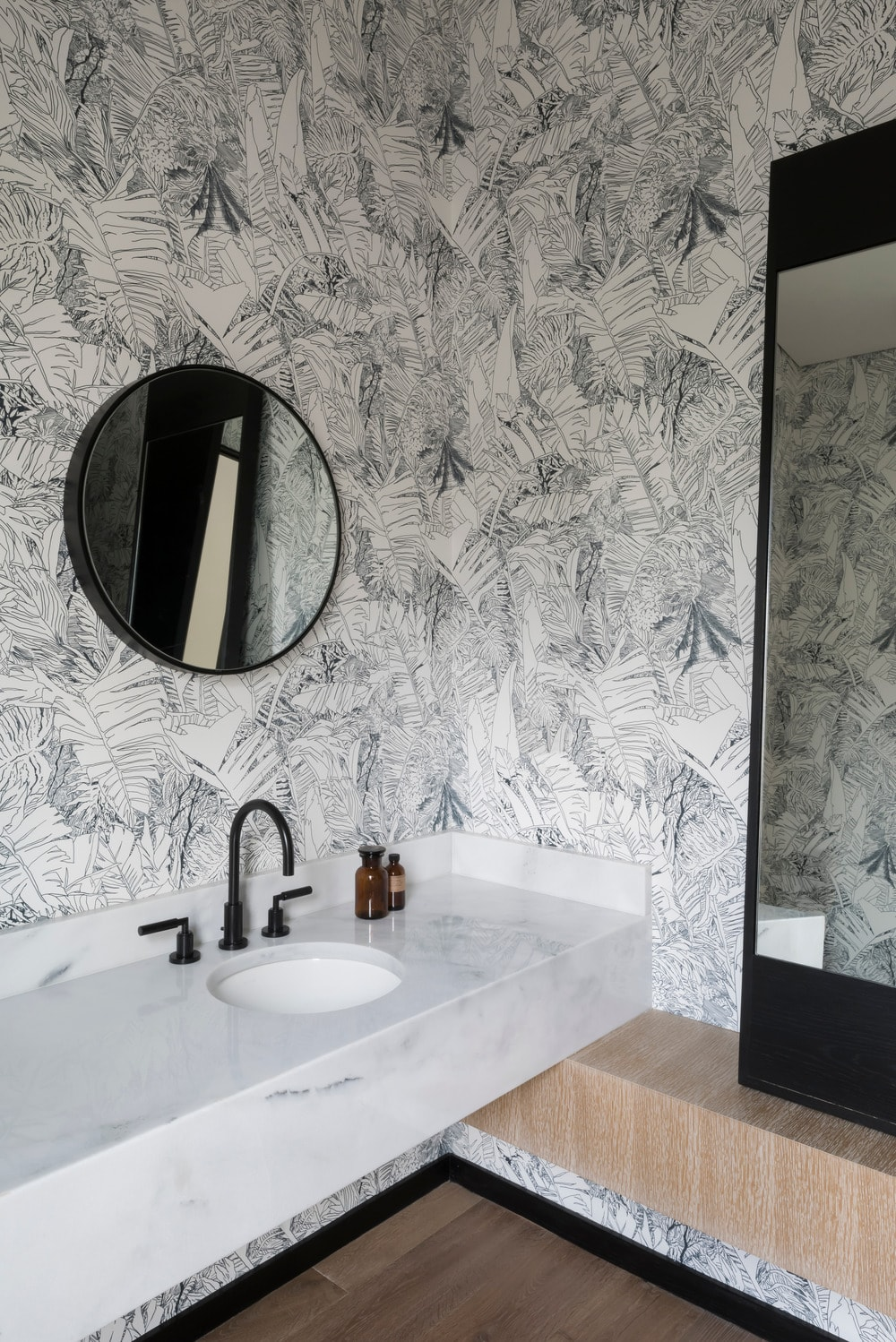This is a close look at the bathroom vanity with a floating white sink, black fixtures and mirrors. These are then complemented by the surrounding wallpaper of palm leaves.