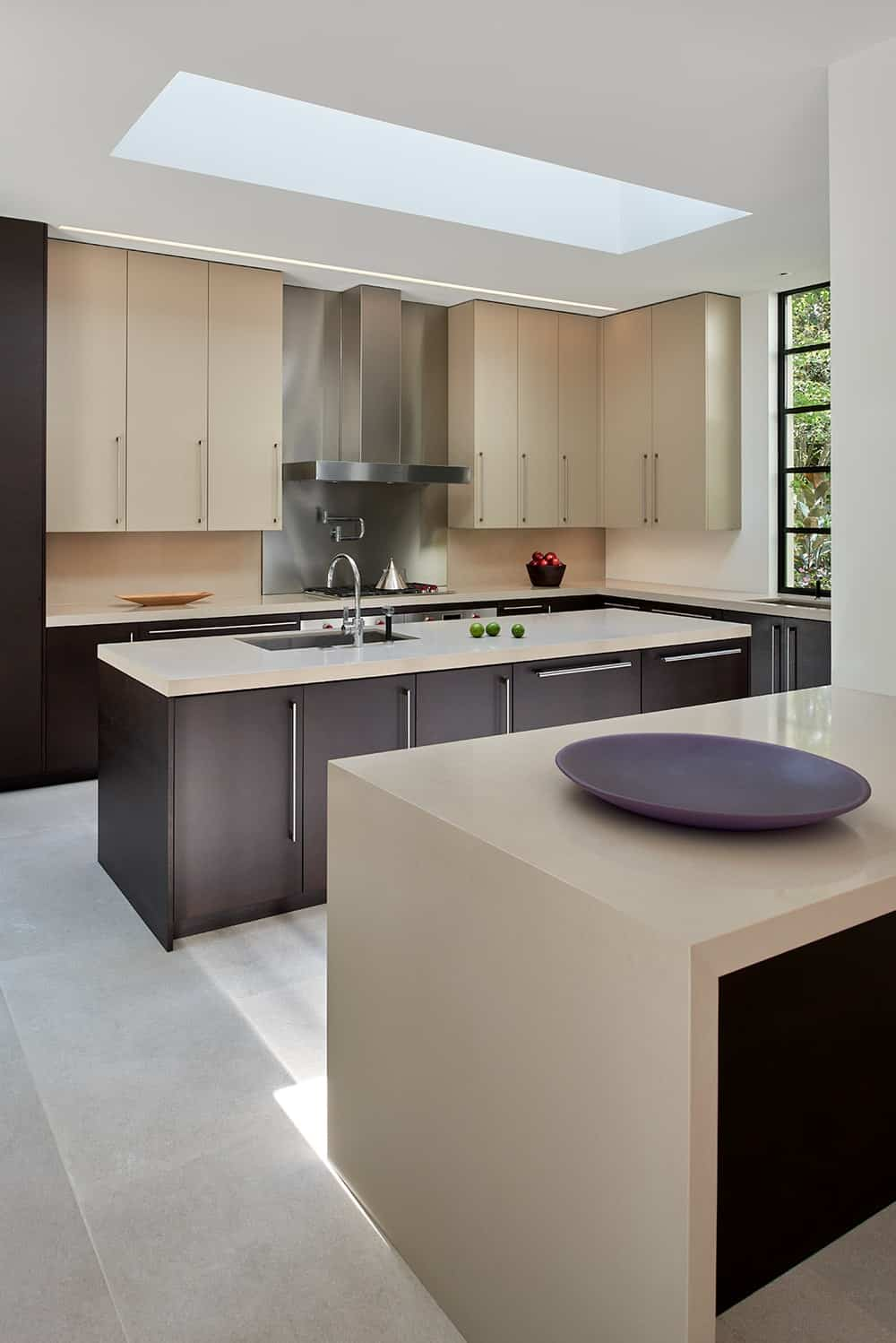 The kitchen has a beige tone to its countertops that match the dark wooden cabinetry contrasted by the bright ceiling and floor.
