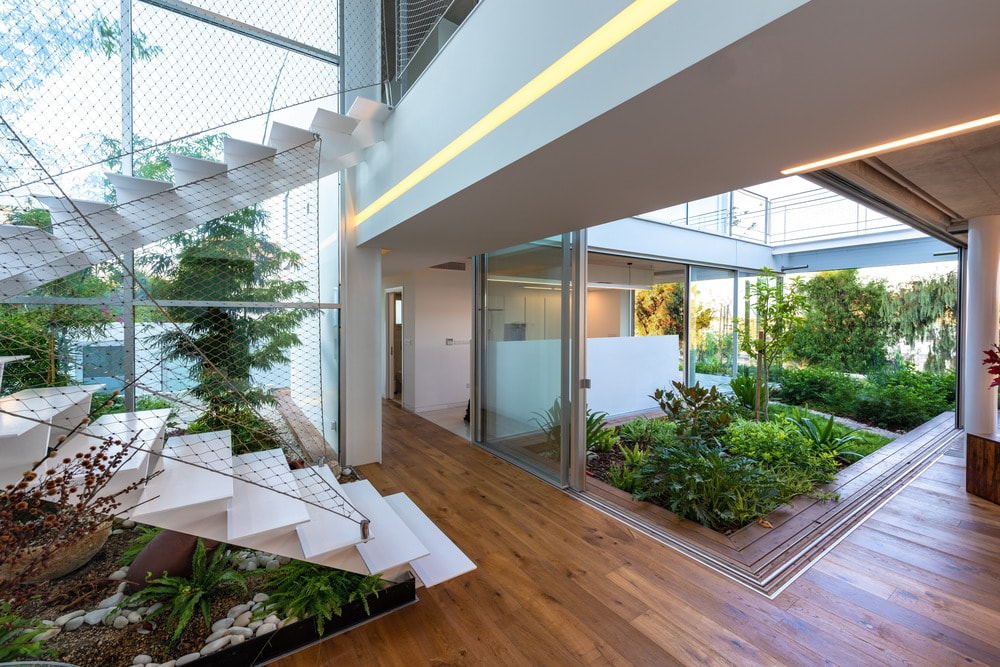 This is a look at the open hallways and walkways of the house in between sections that are adorned with various plants.