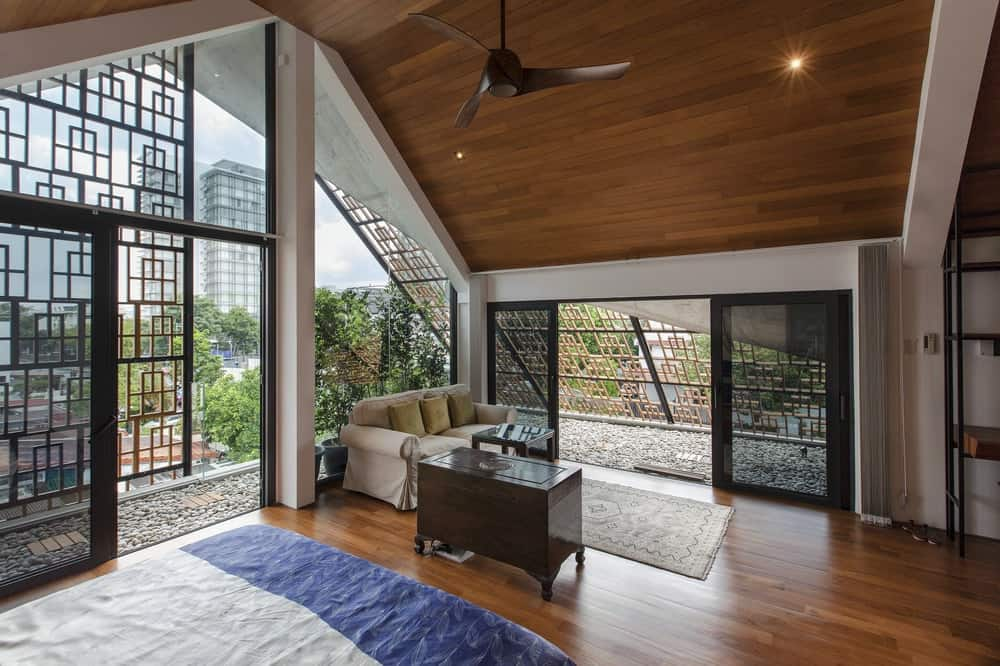 Across from the bed is a sitting area by the balcony with a beige sofa and a dark wooden waist-high cabinet.