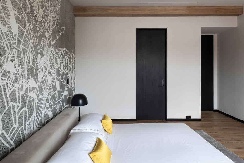 The bedroom has a cushioned bed complemented by the gray wallpaper behind the headboard. These are then complemented by the wooden beams of the ceiling and the hardwood flooring.