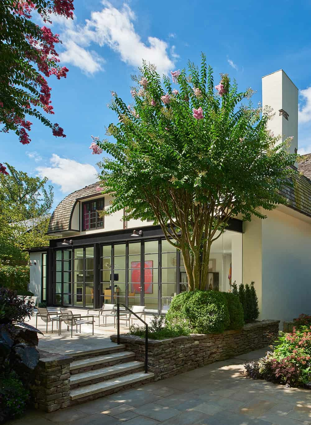 This is the side of the house with wide glass walls that retract to open the kitchen and dining area to the outdoor patio that is adorned with a large flowering tree.