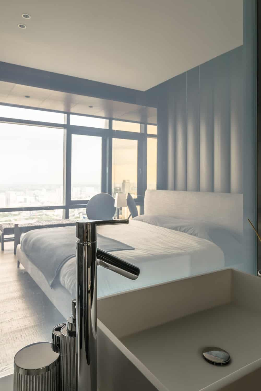 The bathroom is separated from the bedroom by only a glass panel that can be see-through or opaque.