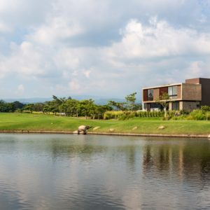 This is a far-off view of the house from the vantage of the large lake showing the lush landscape surrounding the house.