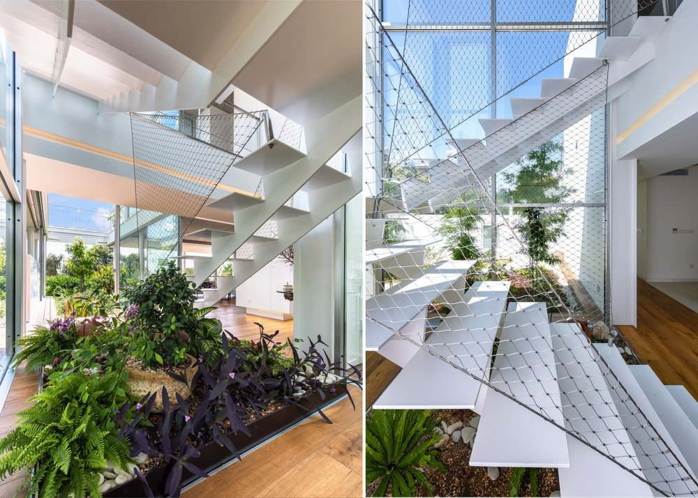 This is a close look at the modern white staircase that has net railings and adorned by plants underneath.