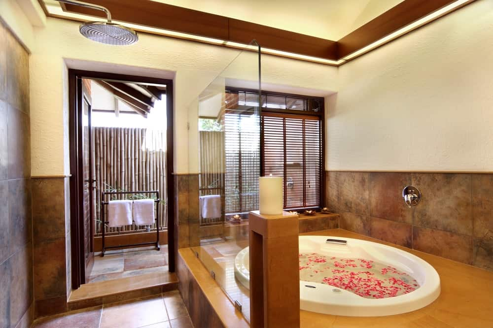 This is the large circular bathtub that stands out against the surrounding dark tiles complemented witha shuttered window on the far side.
