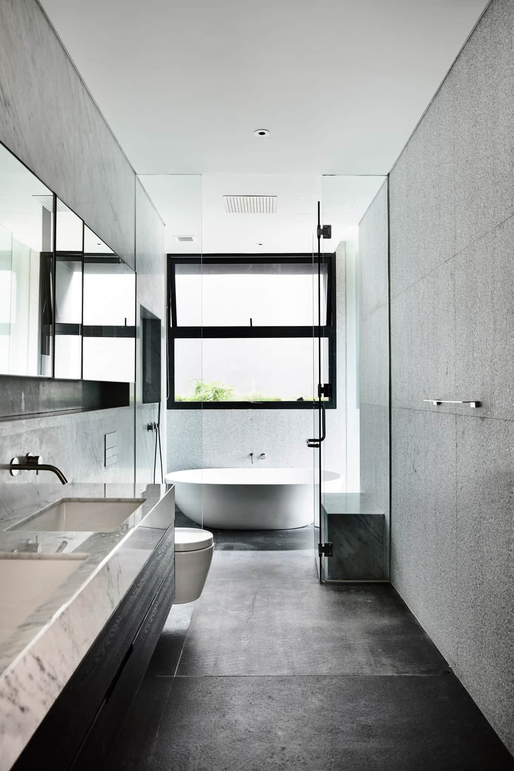 This is a bright and white bathroom with a glass-enclosed wet area at the far edge with a freestanding bathtub.