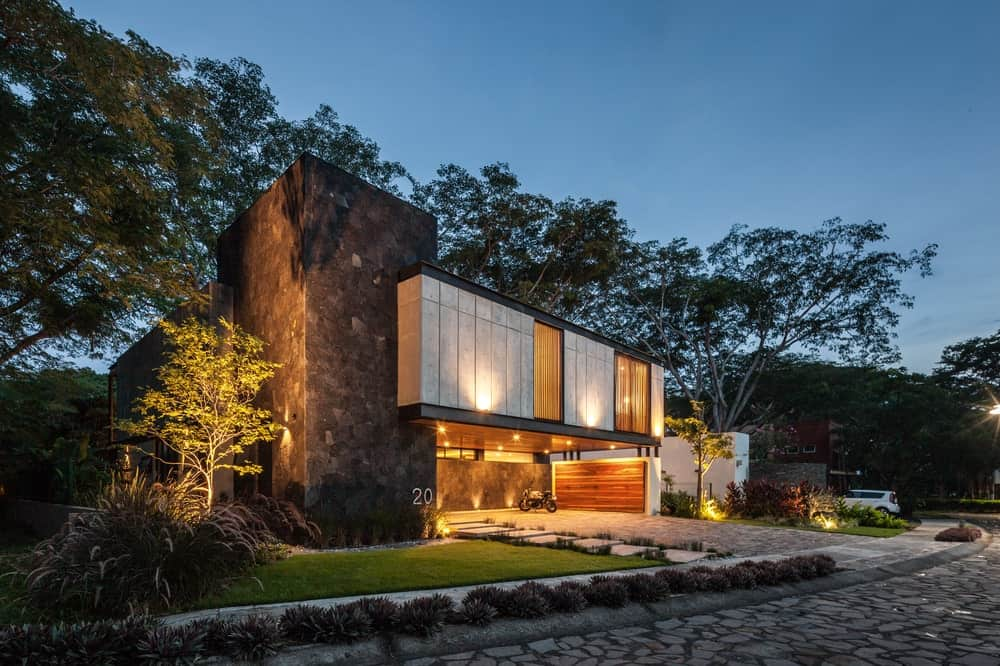 The exterior glow of the house matches with the spotlights that illuminate the concrete walls of the second level.