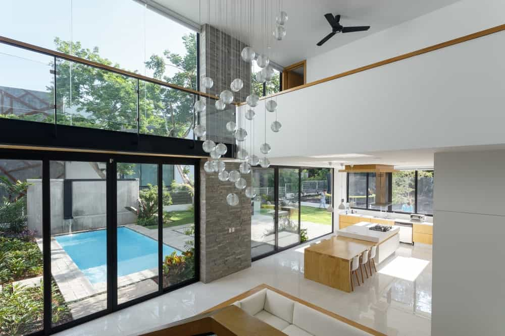 Just inside the glass doors of the poolside area is the conversation pit with a tall ceiling that has an indoor balcony.