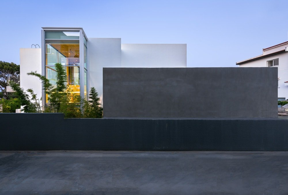 This is an exterior look of the house that has dark outer walls and white exterior walls with glass walls.
