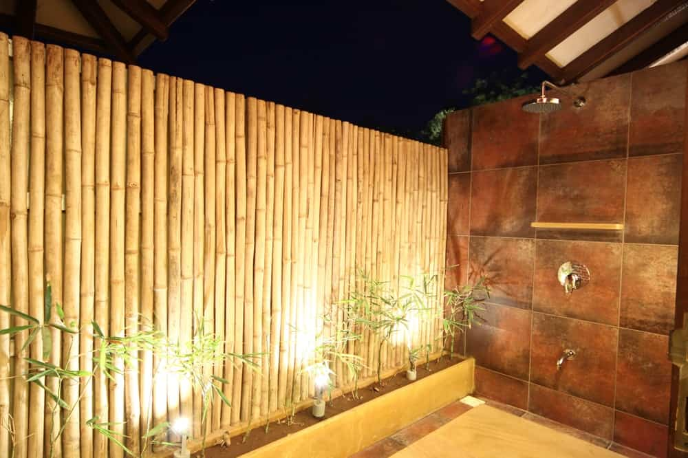 A few steps from the bathtub is this outdoor shower area with a wall of bamboo for privacy.