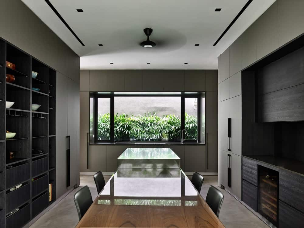 The formal dining room of the house has its won kitchenette and a row of tables that stand out against the surrounding gray tones.