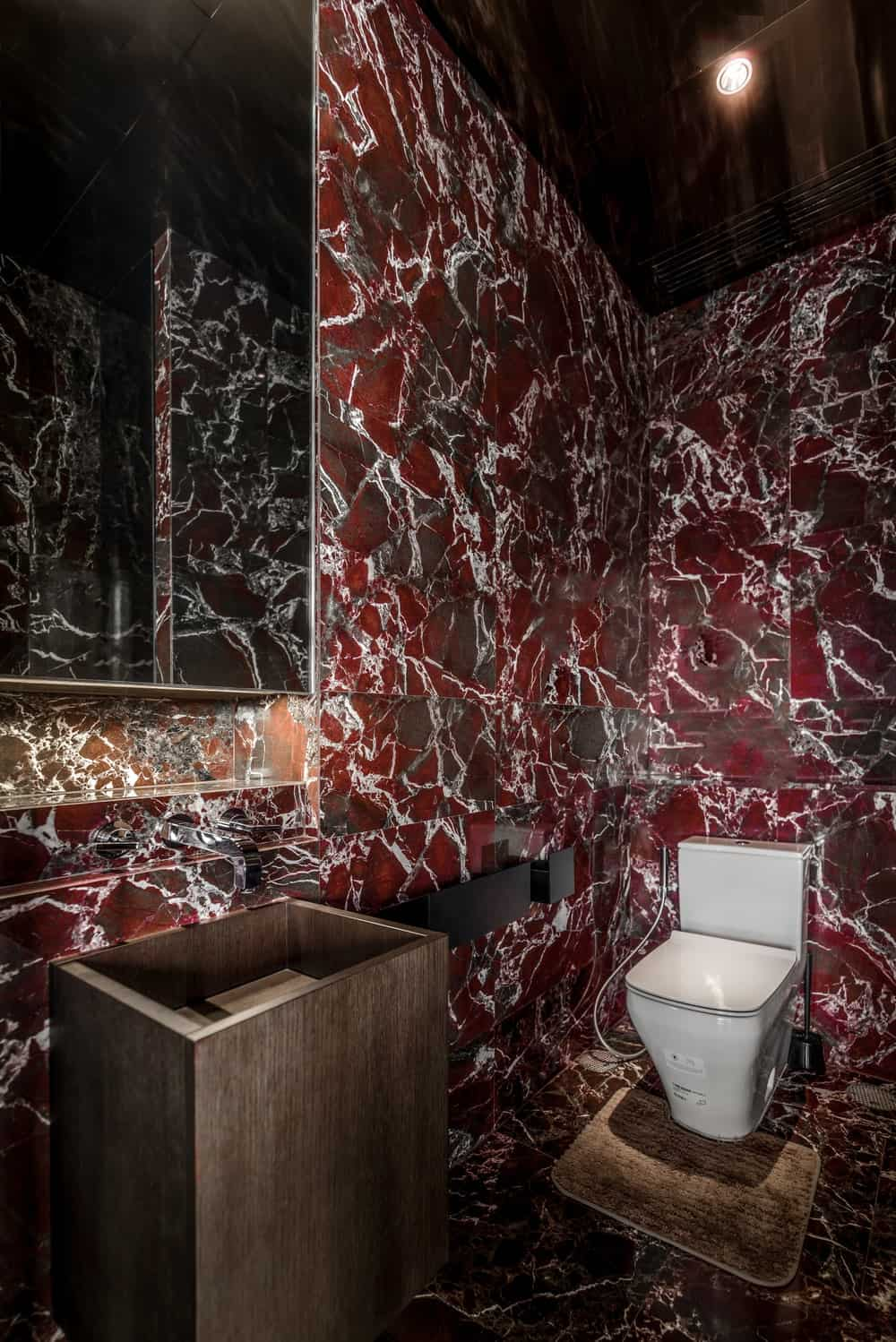 This other bathroom has mosaic red marble tiles that serves as background for the simple white toilet and simple brown sink.