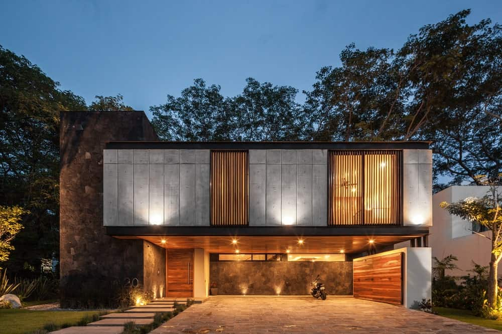 This nighttime view of the house showcases the warm glow of the house from its properly placed lighting and spotlights that give the exterior walls a warm glow.