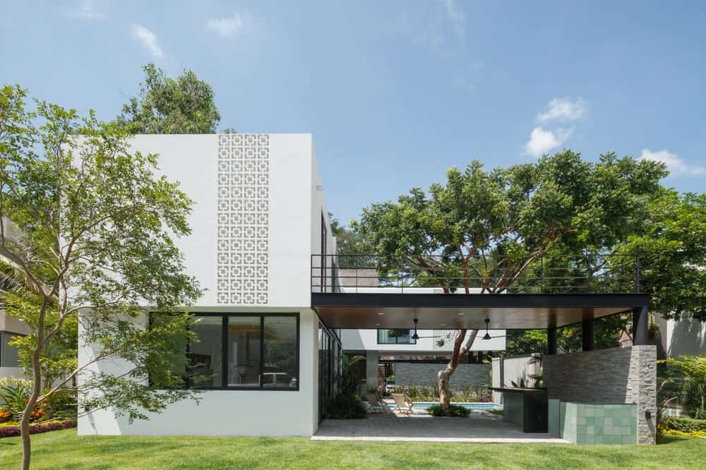 This is the side of the house with a large balcony on the second level and an outdoor kitchen at the ground level adorned by the landscape of tall trees and the swimming pool on the far side.