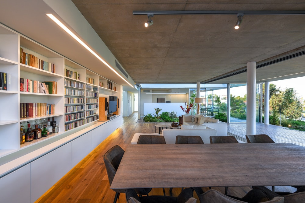 Just behind the sofa of the living room is the large table of the dining area topped with a modern lighting fixture.