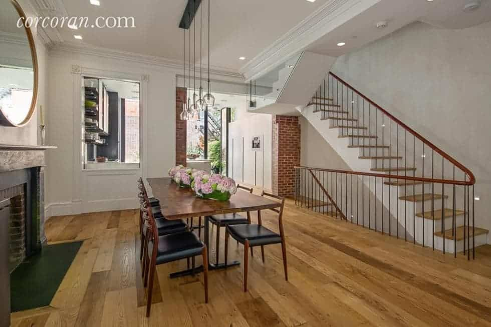 This is the dining room of the townhome that has a long wooden dining table surrounded by cushioned chairs that match the tone of the hardwood flooring. and the banisters of the stairs. Image courtesy of Toptenrealestatedeals.com.