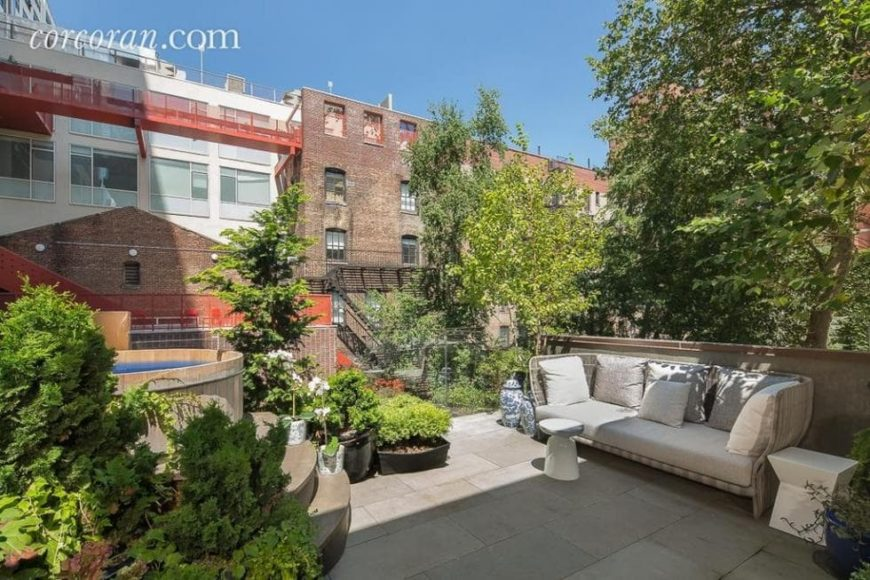 This is the terrace off the primary bedroom of the townhome that features a custom Japanese hot tub surrounded by various potted plants and a comfortable outdoor sofa. Image courtesy of Toptenrealestatedeals.com.