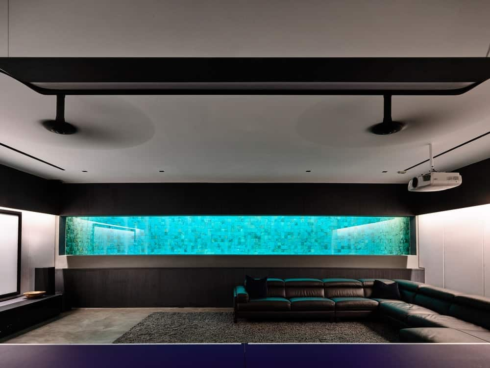 This is the family room with a large and long aquarium on its dark wall overlooking the large L-shaped sectional sofa.