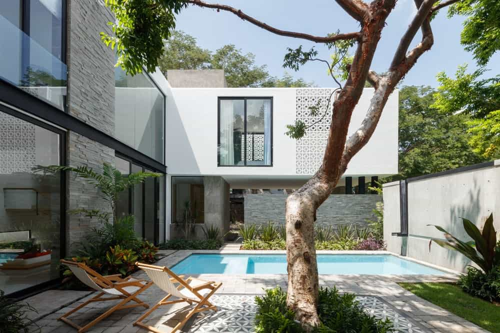 The backyard pool of the house is surrounded by lounge chairs, concrete walkways and small gardens planted on the sides of the house exterior.