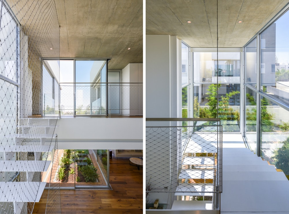 This is the bright second-floor landing with a small indoor balcony that has a net railing and views of the outside through glass walls.
