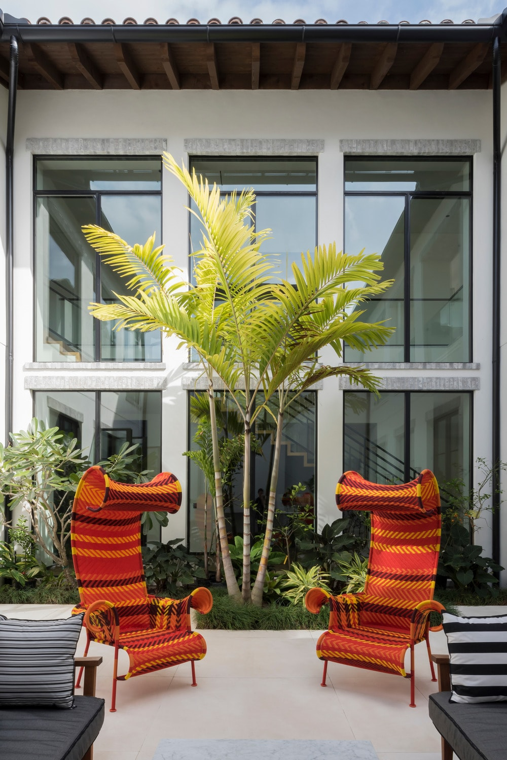 This is a look at the patio just outside the glass walls of the staircase showcasing the two colorful outdoor chairs and the landscaping of tropical plants.