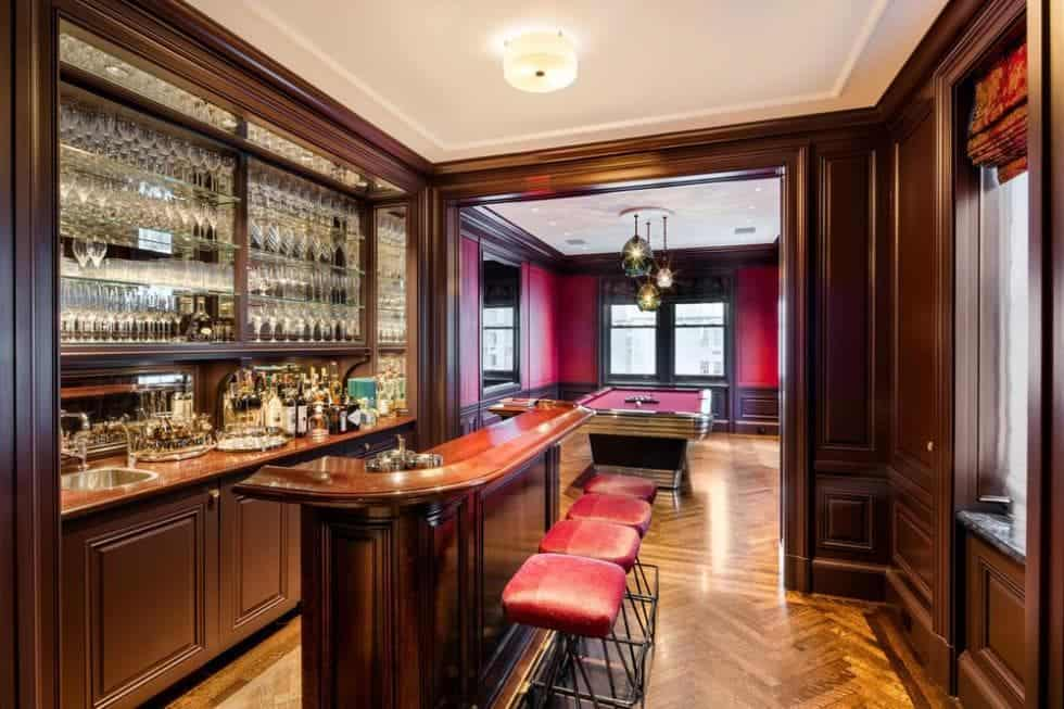 This is the wood-paneled bar that is only a few steps away from the billiards table surrounded by red leather walls on the far side. Image courtesy of Toptenrealestatedeals.com.