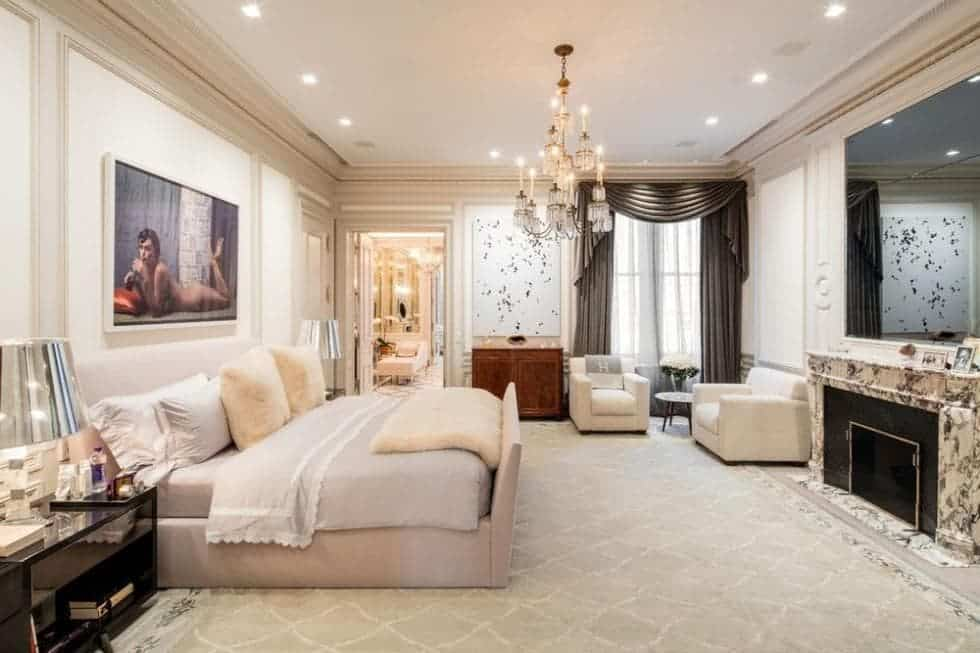 The beige bed blends perfectly with the beige floor, walls and ceiling that has a large crystal chandelier. Image courtesy of Toptenrealestatedeals.com.