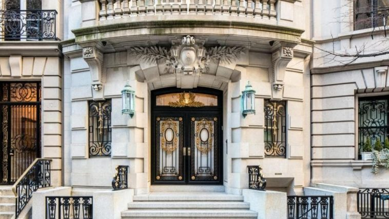 This is the front view of the limestone mansion featuring the main entrance with its elaborate glass main doors with dark frames that make it stand out against the light exteriors with steps from the sidewalk. Image courtesy of Toptenrealestatedeals.com.