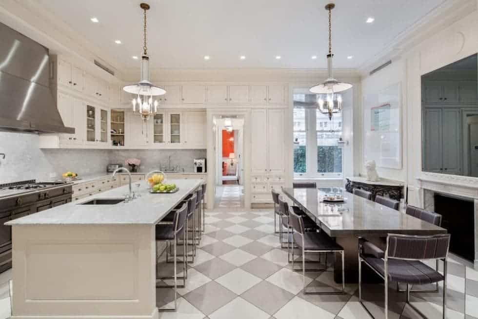 The spacious kitchen has a large kitchen island to pair with the checkered floor. Across from the kitchen island is a large informal dining area by the fireplace. Image courtesy of Toptenrealestatedeals.com.
