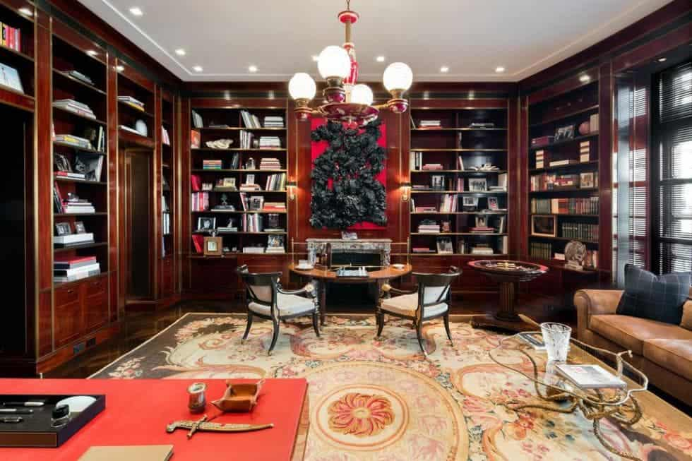 This is the wood-paneled library with built-in wooden bookshelves lining the walls adorned by a large artwork above the fireplace. Image courtesy of Toptenrealestatedeals.com.