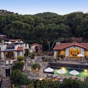 This is an aerial view of the hunting lodge showcasing the main house and a guest house both facing a large pool and outdoor area. These are then complemented by the background of lush landscaping filled with trees. Image courtesy of Toptenrealestatedeals.com.