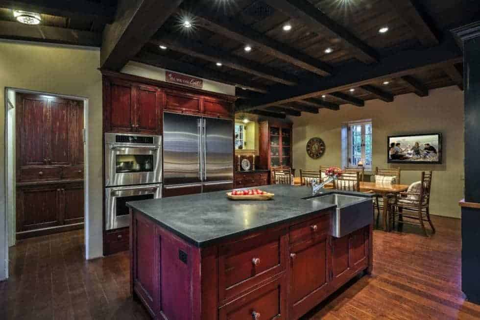This is the spacious kitchen with a tall beamed ceiling that has recessed lights. This is paired with redwood cabinetry that makes the stainless steel appliances stand out. Image courtesy of Toptenrealestatedeals.com.