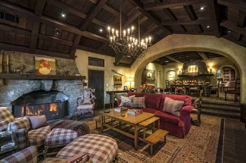 This large room houses the living room area and the dining area at the far end. The living room has a colorful sofa set flanking the wooden coffee table across from the stone fireplace. Image courtesy of Toptenrealestatedeals.com.