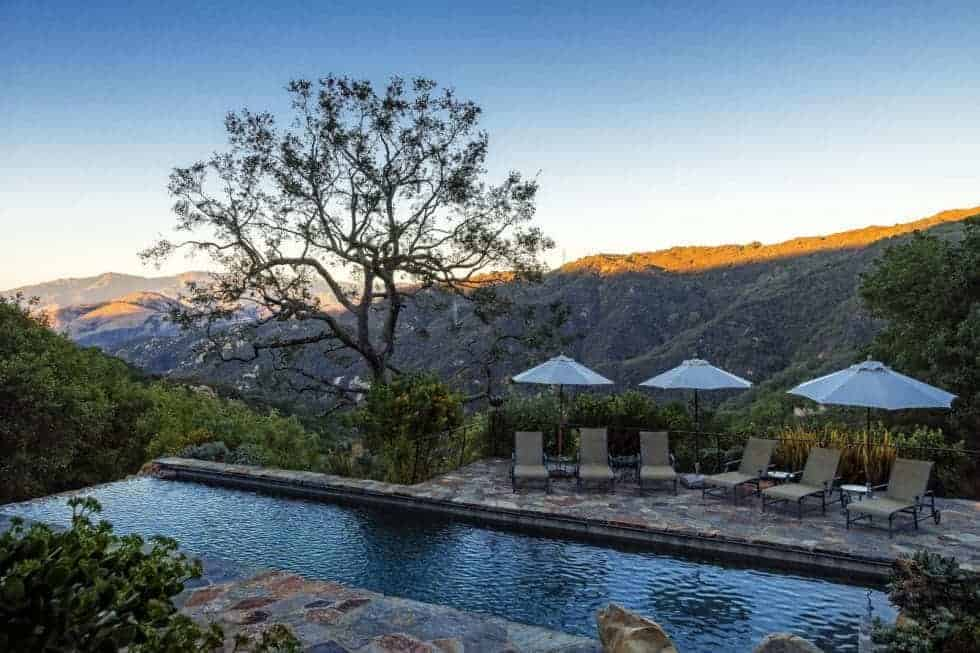 This is a view of the pool that is built on a cliff with a sweeping view of the valley below. The pool is also bordered with stone walkways and shrubs. Image courtesy of Toptenrealestatedeals.com.