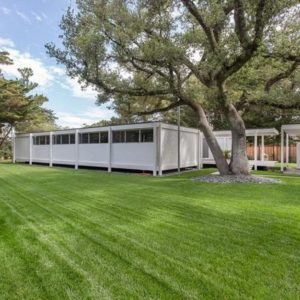 This is the exterior view of the Daphne House with white exterior walls that stand out against the surrounding landscape of wide grass lawns and tall trees. Image courtesy of Toptenrealestatedeals.com.