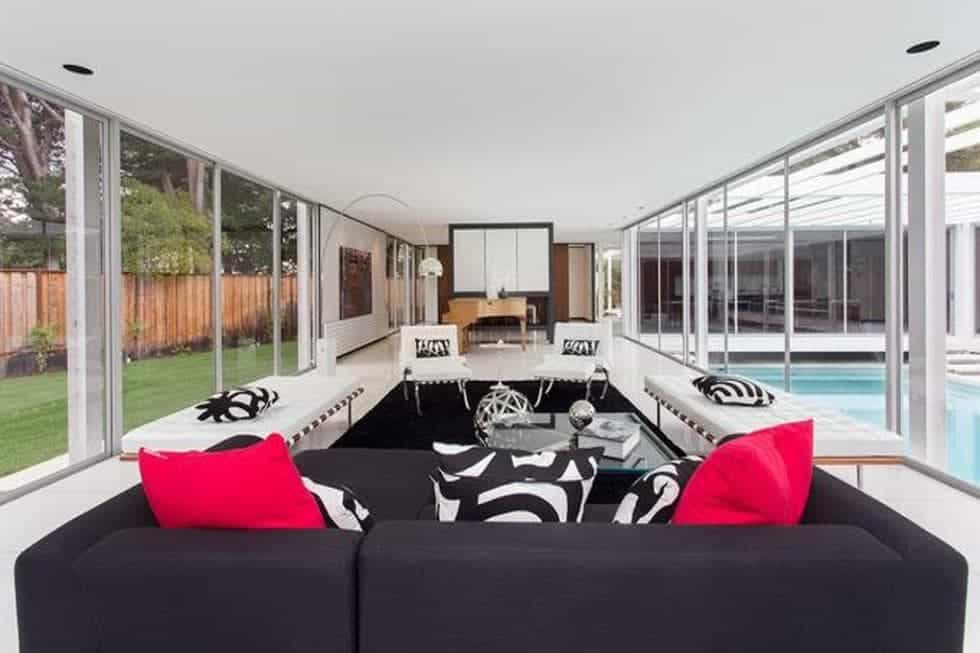 The living room has a dark sofa and a set of white furniture that contrasts the black area rug. These are then complemented by the glass walls on both sides. Image courtesy of Toptenrealestatedeals.com.