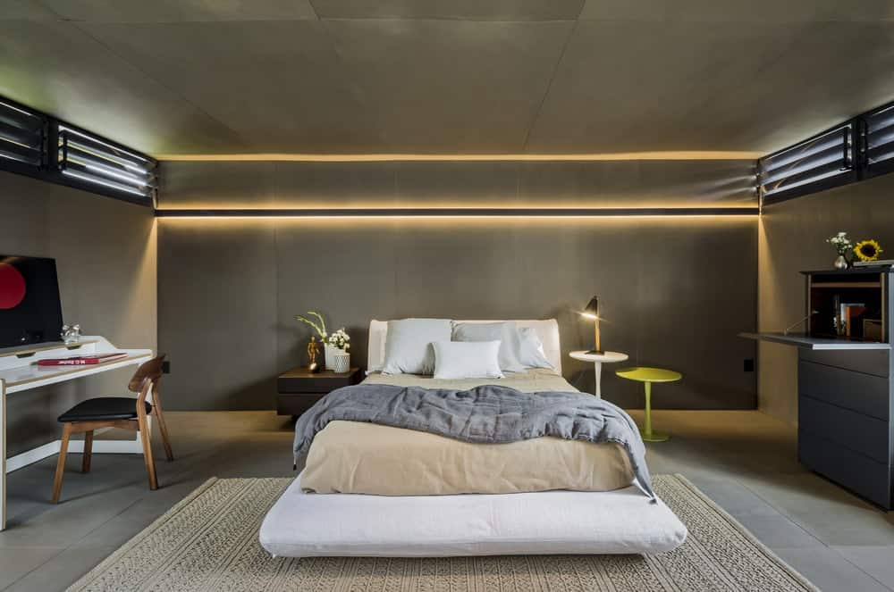 The primary bedroom has a bright platform bed adorned by the warm light of the modern wall lighting.