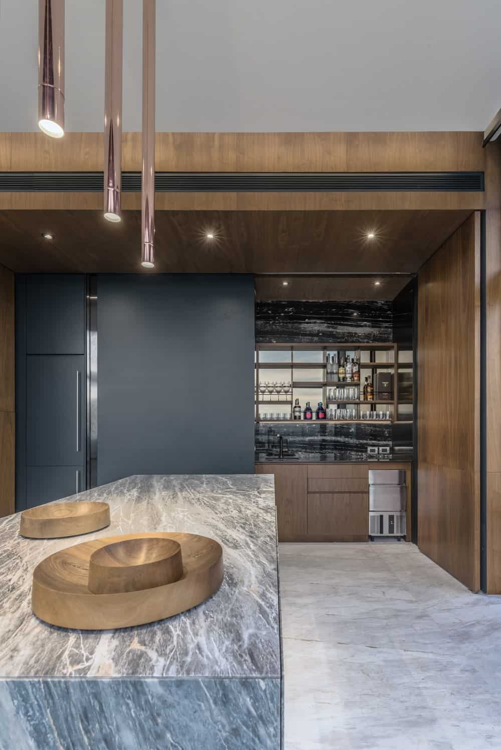 The black structure on the side of the island can also open another way to reveal the liquor cabinet and thus convert the kitchen into a bar.