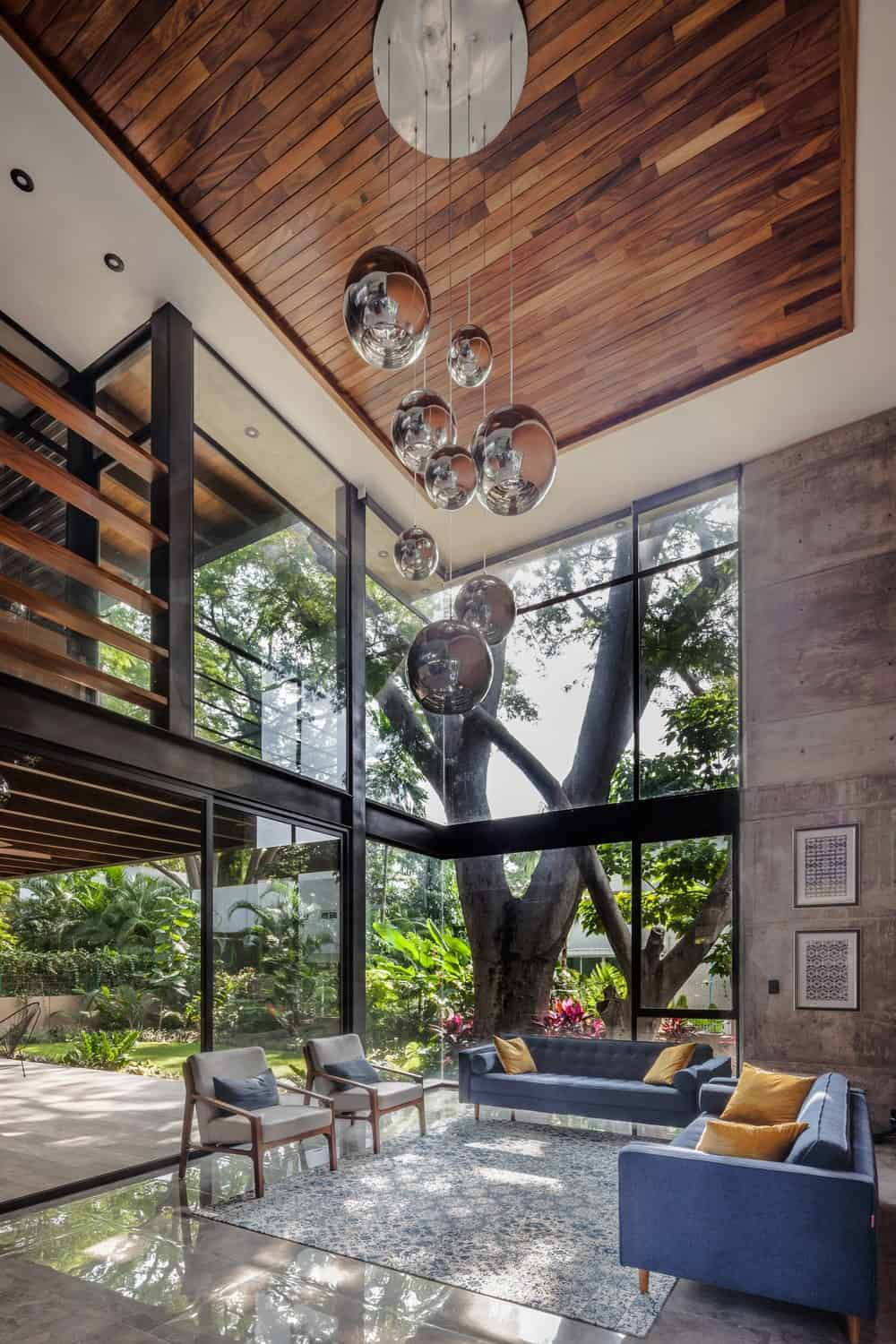 This is the living room with a tall ceiling, tall glass walls and decorative lighting hanging over the sofa sets.