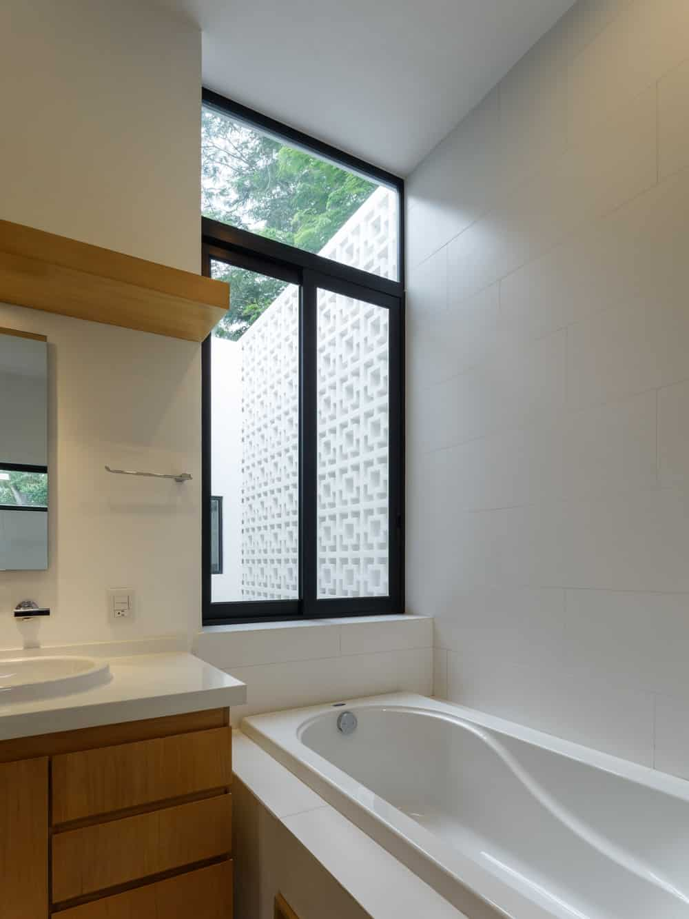 The bathroom has a large window above the head of the bathtub beside the wooden vanity with wooden drawers.