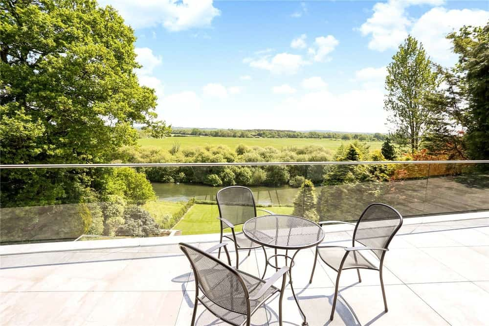 This is a balcony fitted with an outdoor dining set and complemented by the scenery of the landscape and the glass railings.