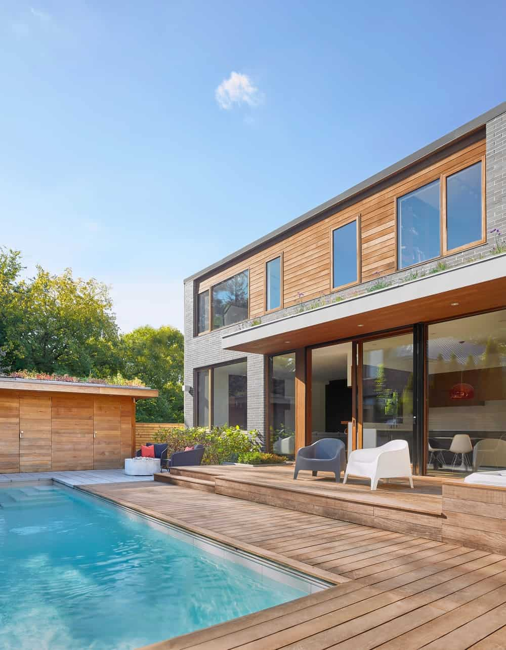 This is a view of the back of the house showcasing the wooden deck flooring of the poolside area that match with the exteriors of the house with large windows.