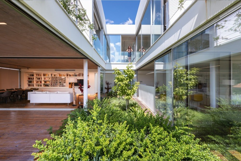 This landscaped middle area is flanked by sliding glass walls that open to the interior.