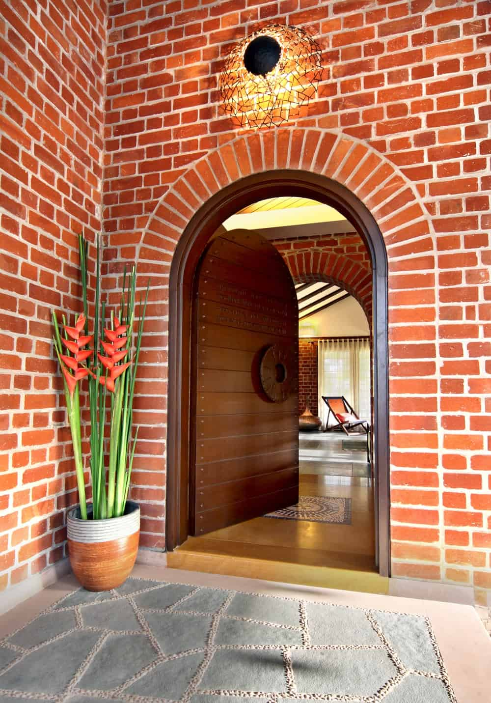 This is a look at the main entrance of the house with a wooden arched main door adorned with a potted plant on the side.