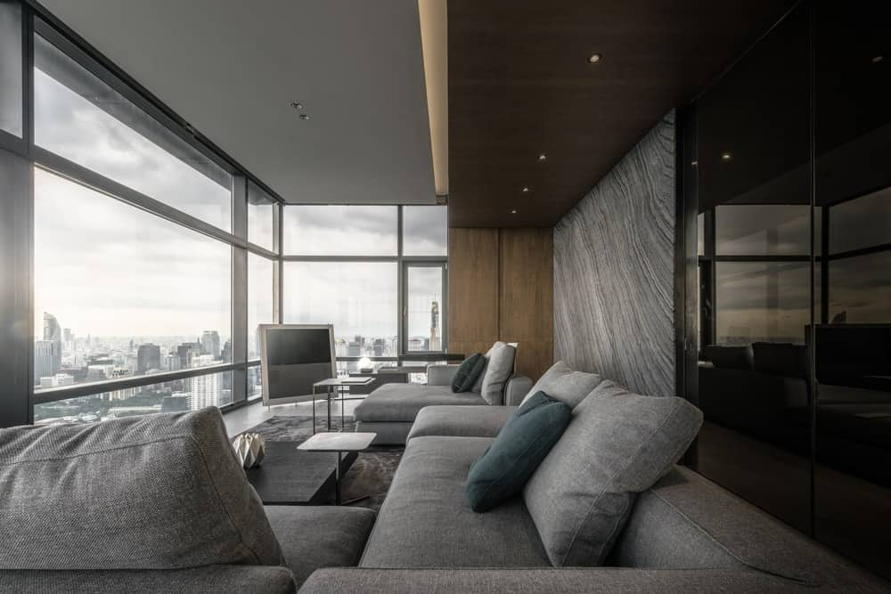 This is a close look at the comfortable gray U-shaped sectional sofa that is brightened by the glass walls.