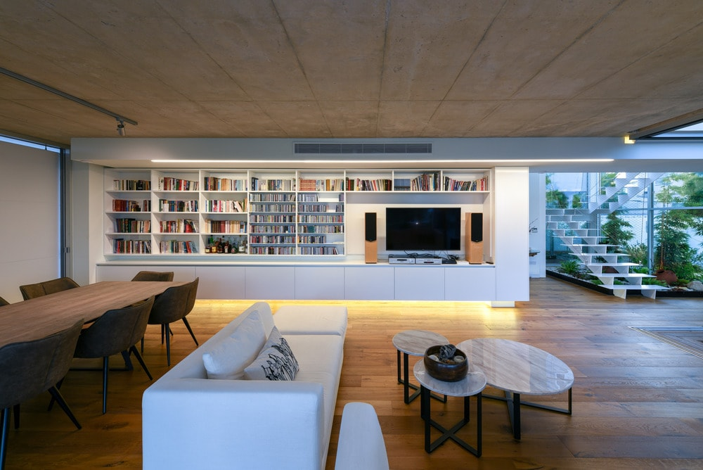 On the other side of the living room is a large walls with built-in wooden shelves and cabinets that serve as bookshelves and entertainment cabinet.