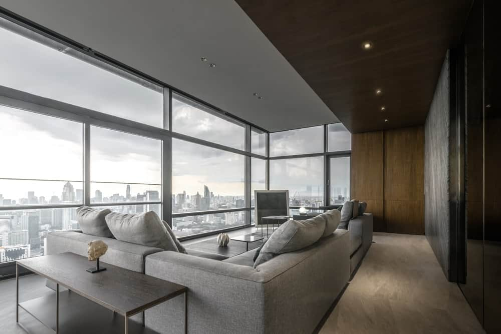 This is a view of the large and spacious living room showcasing the natural lights coming in from the glass walls.