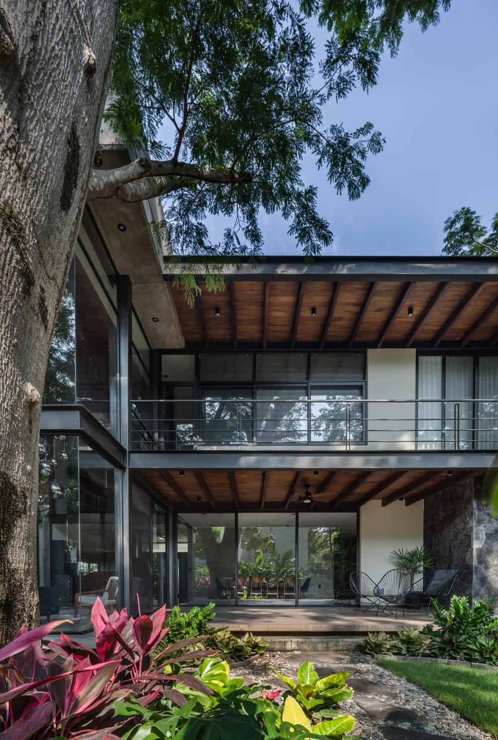This view of the back of the house showcases the beamed ceiling of the balcony and the patio nderneath.