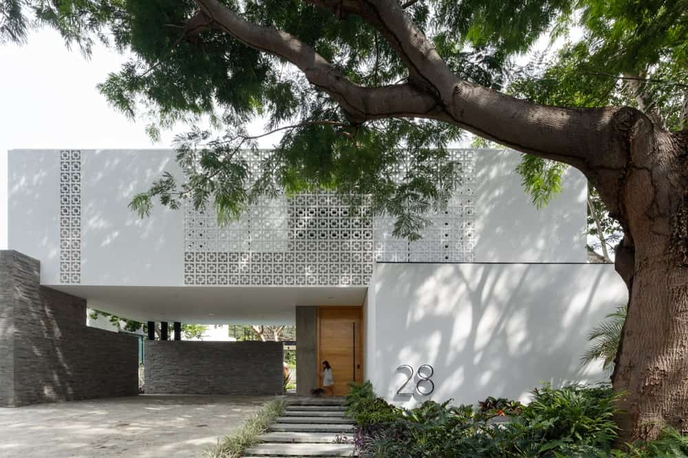 This is the front view of the house with white exterior walls adorned by the see through pattened panels of the second level.